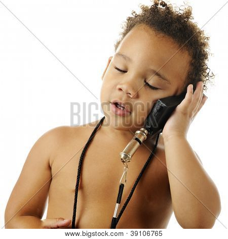 An adorable, bare-chested preschooler, eyes closed, pretending to talk on a cell phone.  On a white background.