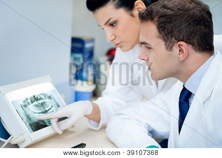 Dentist and assistant analyzing x-ray at the dental clinic