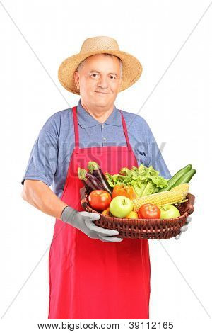Mature farmer man holding a basket with fresh vegetables isolated on white background