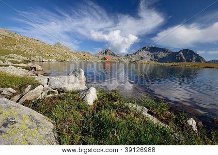 Tevno Lake in Pirin Mountain Bulgaria beautiful sky and hut