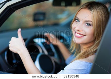 Smiling young woman sitting in car