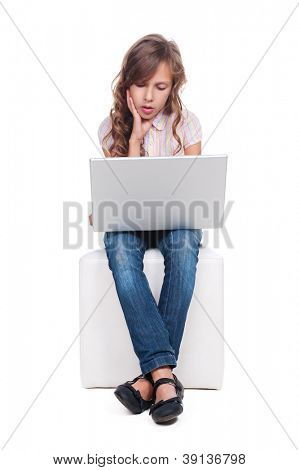 ten year girl is boring and looking at the laptop. isolated on white background