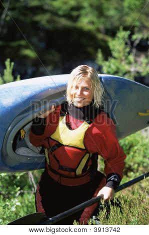 Woman Carrying Canoe Whilst Smiling