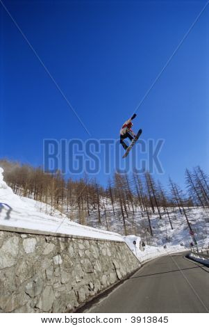 Man Doing Jump Across Mountain On Snowboard