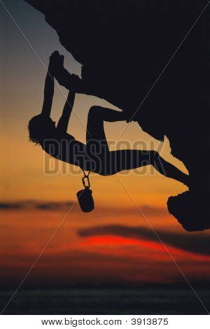 Woman Cliff Climbing Over Ocean At Dusk