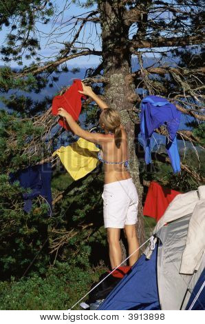 Woman Hanging Up Washing By Tent
