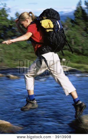 Woman Hopping Across Rocks Over River
