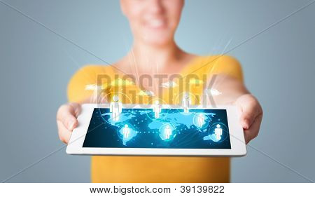 Beautiful young woman holding modern tablet with social icons