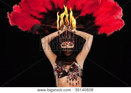 A bellydancer with fire headdress and feathers