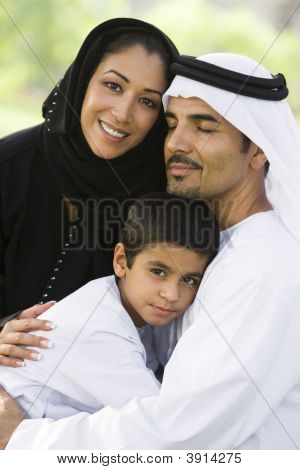 Middle Eastern Family Sat On Grass In Park