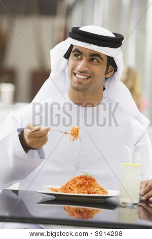 Middle Eastern Man Eating And Drinking In Shopping Mall