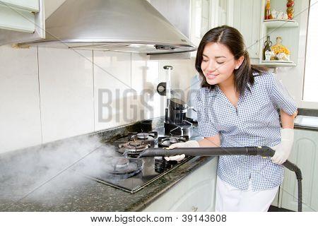 Modern kitchen - happy woman steam cleaning