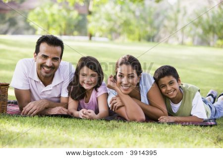 Middle Eastern Family Laid On Picnic Blanket In Park