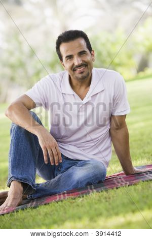 nahöstlichen Mann saß auf Picknickdecke im park