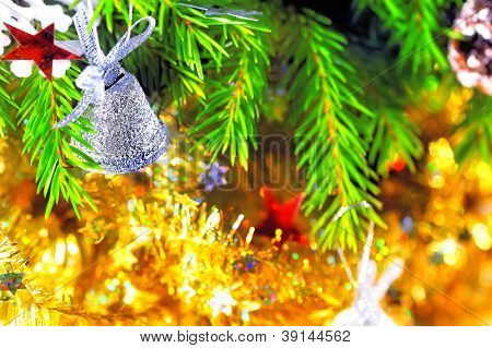 Silver bell hanging on the branch of a Christmas tree