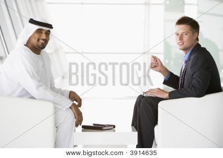Middle Eastern And Western Man Discussing Business