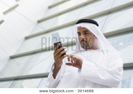 Middle Eastern Business Man Stood Outside Offices Using Cell Phone