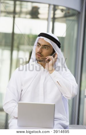Middle Eastern Business With Man On Laptopn And Cell Phone
