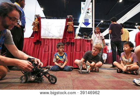 SUBANG JAYA - NOVEMBER 10: An unidentified robotics expert gets the visitors' attention with a motorcycle robot in the World Robot Olympaid KL 2012 on November 10, 2012 in Subang Jaya, Malaysia.
