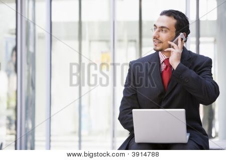 Middle Eastern Business Man On Cell Phone Using Laptop