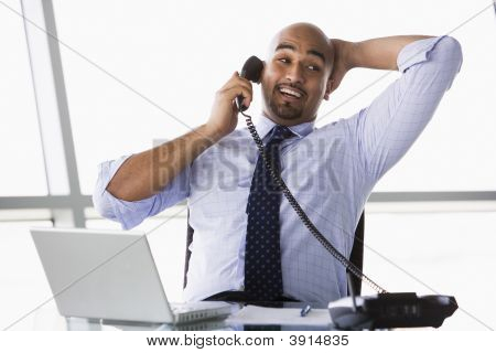 Middle Eastern Business Man At Desk Using Phone And Laptop