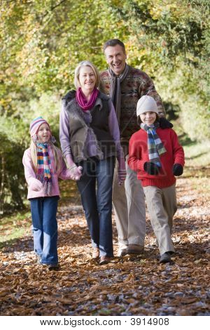 Children With Grandparents Walking Through Woodland