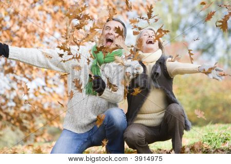 Couple Playing In Leaves