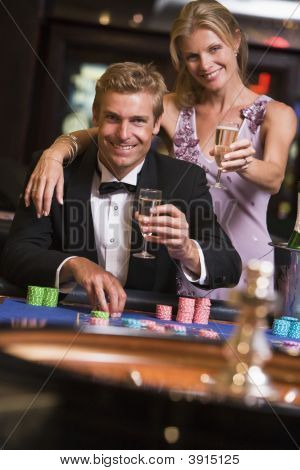 Man And Woman Playing Roulette With Champagne