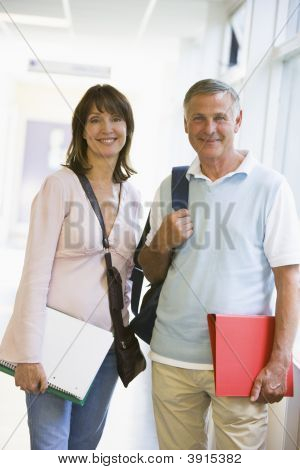 Man And Woman Stood In School Corridor