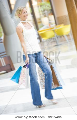 Woman In Shopping Mall With Bags