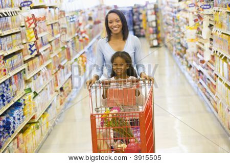 Woman And Child Pushing Trolley In Supermarket