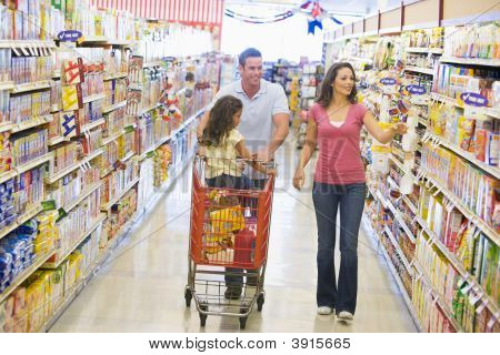 Family Pushing Trolley In Supermarket