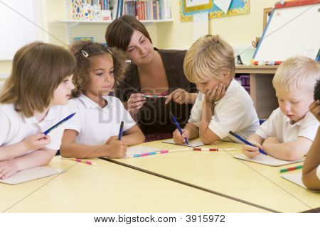 Teacher Helping Class With Numeracy