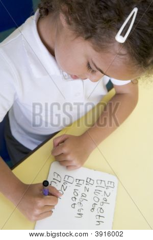 Portrait Of Child Writing Name On White Board