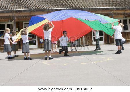 Crianças usando o pára-quedas para aprender na escola parque