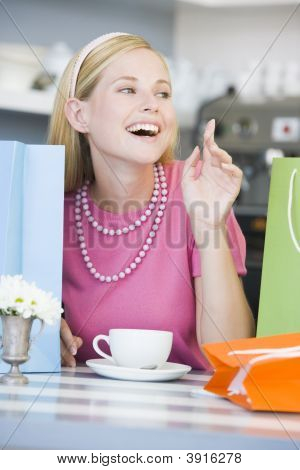 Woman Raising Hand In Tea Room With Shopping Bags