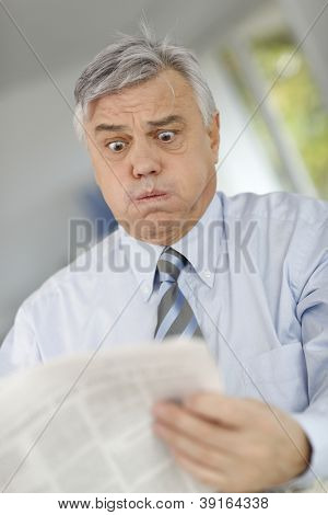 Senior businessman reading newspaper with horrified look