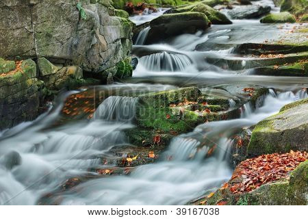 Small cascade on autumn mountain stream