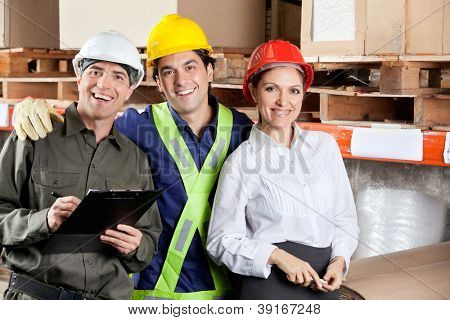 Portrait of young foreman with supervisors smiling together at warehouse