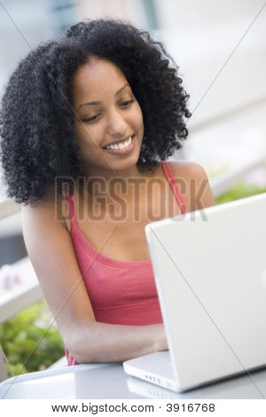 Woman Sitting At Table Outdoors With Laptop Smiling (High Key)
