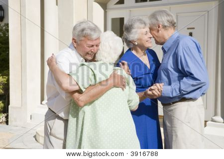 Two Senior Couples Greeting Each Other With Open Arms