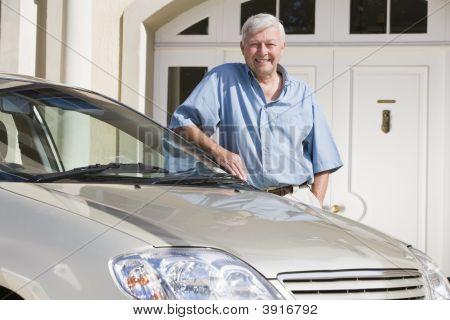 Alter Mann mit seinem Auto außerhalb seiner Heimat