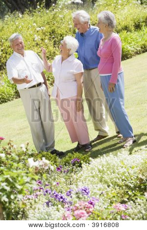Two Senior Couples In A Flower Garden