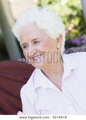 Senior Woman im Freien sitzen auf einem Stuhl