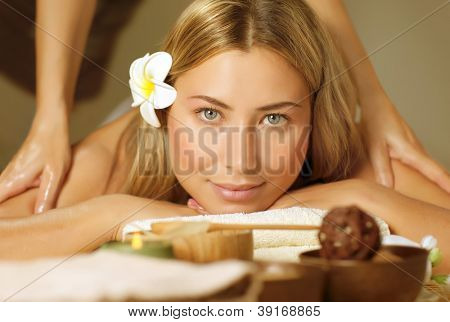 Image of beautiful woman laying down and relaxed on massage table, pretty blond girl enjoying dayspa, alternative medicine, masseur doing antistress massaging for cute patient, luxury spa salon