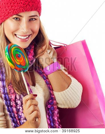 Photo of young beautiful woman lick big colorful lollipop and holding pink paper bag, pretty girl wearing red stylish hat and eating sugar candy isolated on white background, christmastime sweets