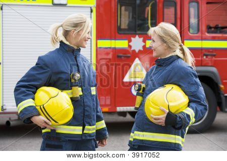 Two Firewomen Standing By Fire Engine Talking
