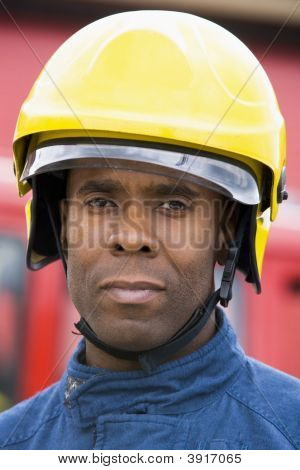 Fireman Standing By Fire Engine Wearing Helmet