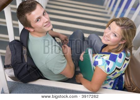 Two Students Sitting On Staircase With Notebooks (Selective Focus)