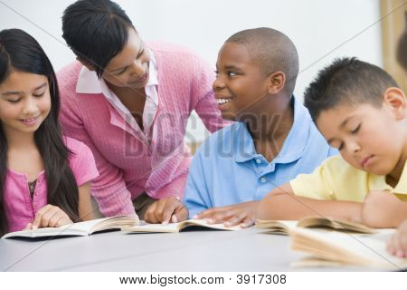 Students In Class Reading With Teacher Helping (Selective Focus)